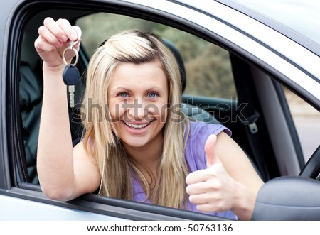 Charming female driver showing a key with a thumb up after buying a new car - stock photo