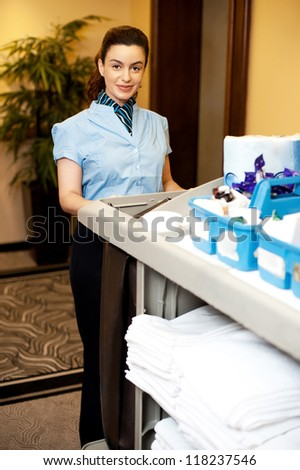 Charming female executive holding toiletries cart and posing in front of camera - stock photo