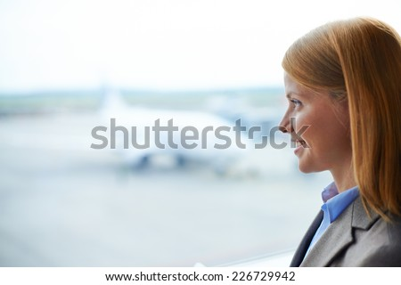 Charming female in formalwear looking through window in airport - stock photo