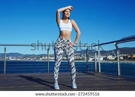 Charming female runner holding hand above her forehead while taking a break after fitness training outdoors, athletic woman in sportswear standing on wooden pier of beautiful Mediterranean coastline - stock photo