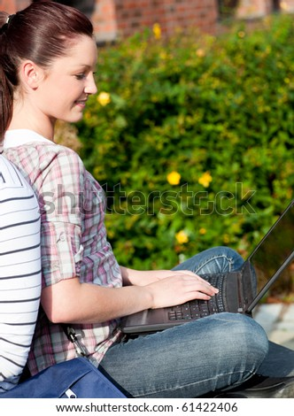 Charming female student using a laptop and sitting behind her boyfriend in the park of their university