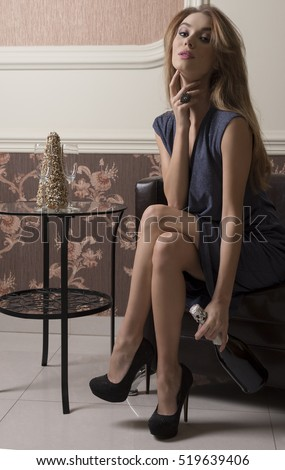 charming female with evening blue dress and heels is sitting in elegant ambient with a bottle of champagne and flutes. Ready for toast. Rich luxurious party