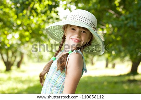 Charming girl in a big wicker hat