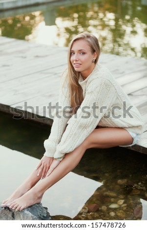 Charming girl in sweater near the water - stock photo