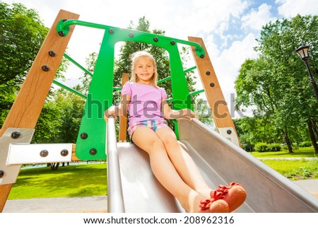 Charming girl on playground chute ready to slide