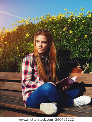 Charming girl relaxing in the spring park while read book, female student sitting on wooden bench at campus, attractive blonde hair young woman enjoying the sun at beautiful day outdoors, filter sun - stock photo
