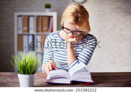 Charming girl sitting by wooden table and reading book - stock photo