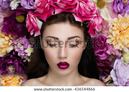 Charming girl with an angelic face and a beautiful accessories flower big pink roses background. Pretty young lady pink lips perfect shape brown eyebrows eyes, make up skin texture shadows. Sadness - stock photo
