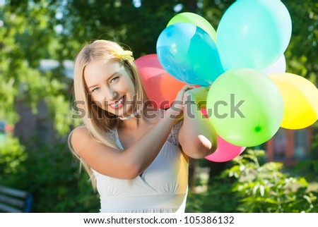 Charming girl with balloons at the festival - stock photo
