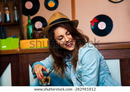 charming girl with cocktail in hand laughing at the bar counter. horizontal photo - stock photo