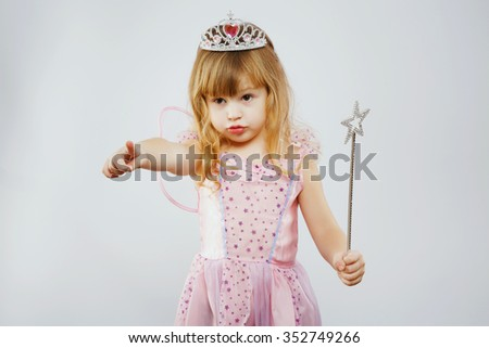Charming girl, with curly blond hair, wearing on pink dress, silver crown and fairy wings, posing with magic stick, on white background, in studio, waist up - stock photo