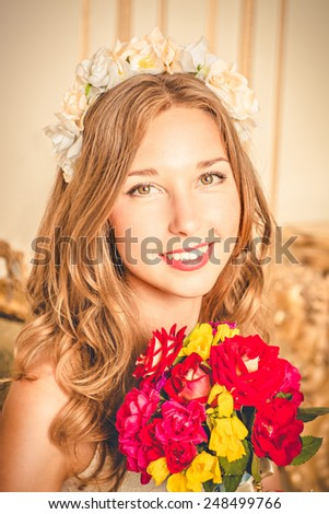 charming girl with flower wreath on head and with a bouquet in hands smiling.  - stock photo