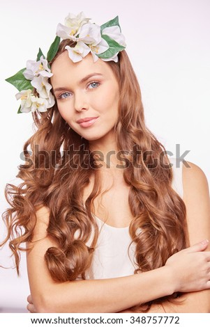 Charming girl with long beautiful curly hair wearing floral wreath