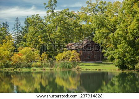charming gorgeous view of old vintage wooden abandoned cabin, standing in woods reflected in lake calm water on sunny warm autumn day - stock photo