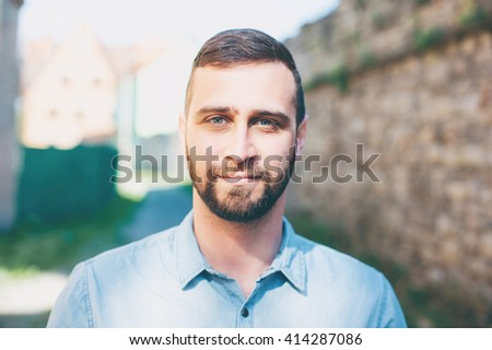Charming handsome. Close up portrait of Attractive young bearded man looking at camera outdoors - stock photo