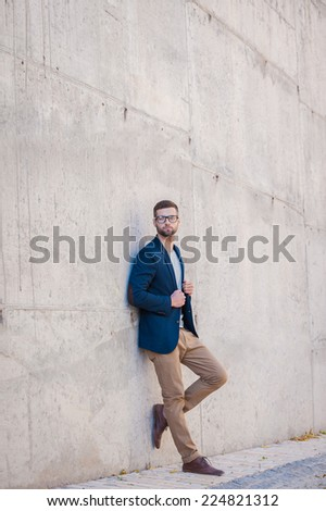 Charming handsome. Full length of handsome young man in smart jacket leaning at the concrete wall outdoors - stock photo