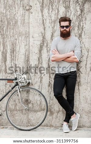 Charming handsome. Full length of young bearded man keeping arms crossed and looking at camera while standing near his bicycle against the concrete wall - stock photo