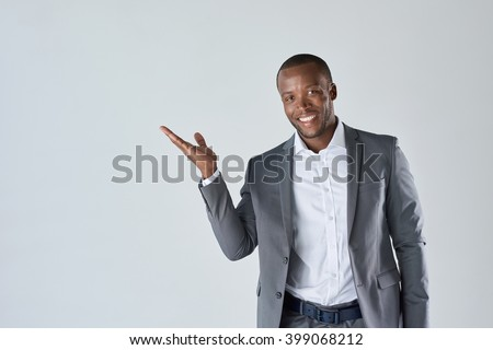 Charming handsome young black business man holding his hand up to show present sell product - stock photo