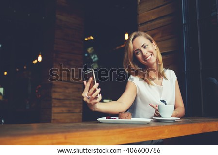 Charming happy hipster girl photographing herself on cell telephone camera while relaxing in modern coffee shop, pretty woman with cute smile making self photo on her smart phone during rest in cafe  - stock photo