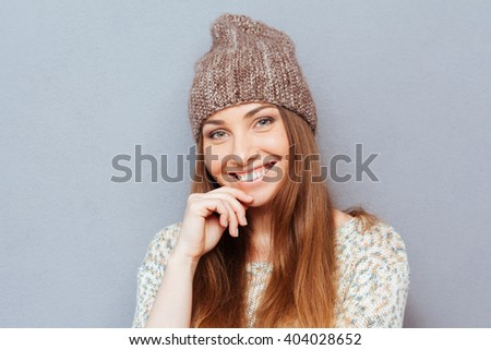 Charming happy woman looking at camera over gray backgorund - stock photo