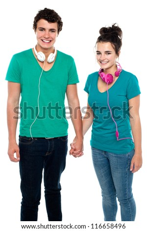 Charming happy young couple with headphones around their necks, holding hands. Great bonding - stock photo
