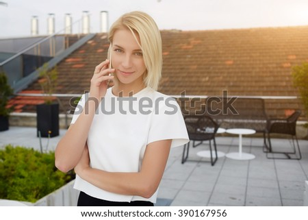 Charming hipster girl is phoning via mobile phone, while is standing on a terrace cafe`s in summer day during free time. Attractive female is calling via cell telephone during her rest in coffee shop - stock photo