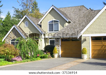 charming house with peaks and lush landscaping - stock photo