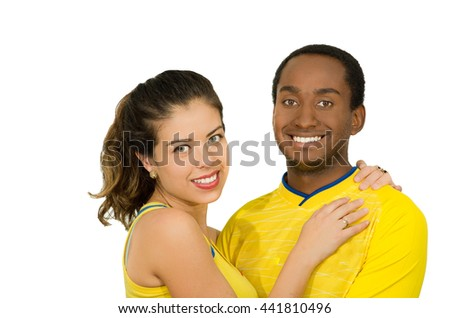 Charming interracial couple wearing yellow football shirts, embracing friendly while posing for camera, white studio background - stock photo