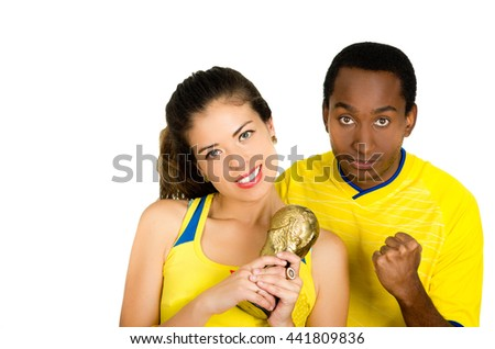 Charming interracial couple wearing yellow football shirts holding small trophy posing for camera, white studio background - stock photo