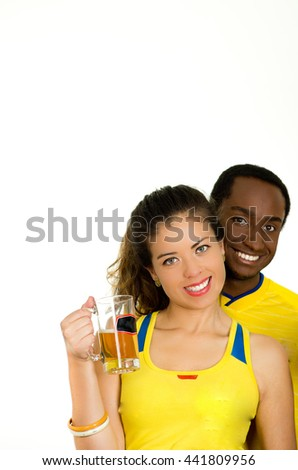 Charming interracial couple wearing yellow football shirts, posing for camera holding beer glass and smiling, white studio background - stock photo