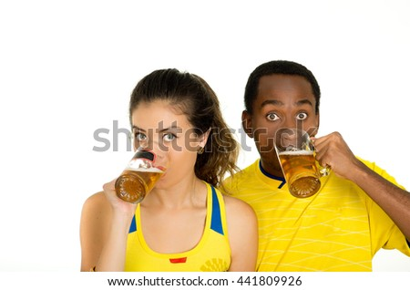 Charming interracial couple wearing yellow football shirts, posing for camera holding beer glasses and smiling, white studio background - stock photo