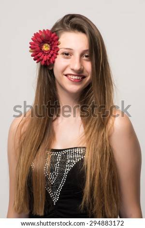 Charming lady with red flower touching cheeks with innocent and joyful smile - stock photo