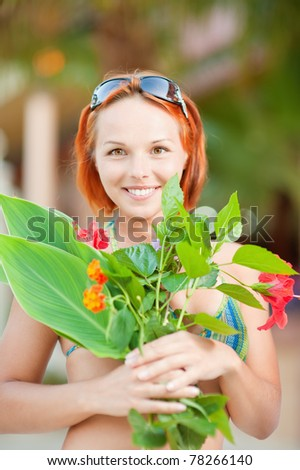 Charming laughing woman has control over bunch of flowers, against summer green park. - stock photo
