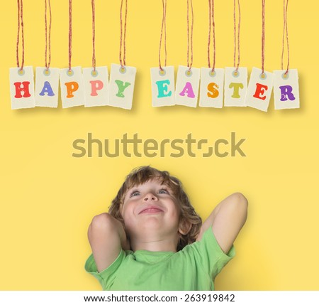 Charming little boy looking up to  Happy Easter banner isolated on yellow background  - stock photo