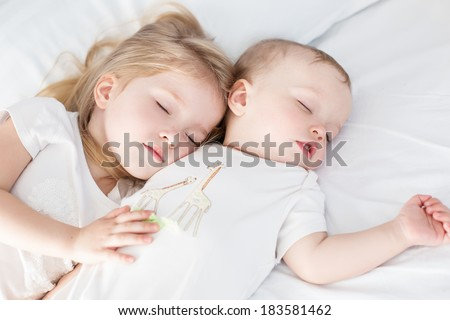 charming little brother and sister asleep embracing on white background - stock photo