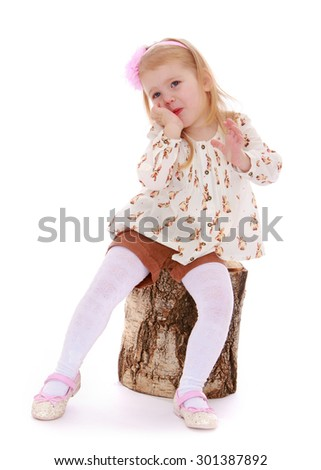 Charming little Caucasian girl with blond hair on his head that adheres to the rim in the form of roses sitting on a birch stump. Girl covers her face with her hand, she seems shy-Isolated on white - stock photo