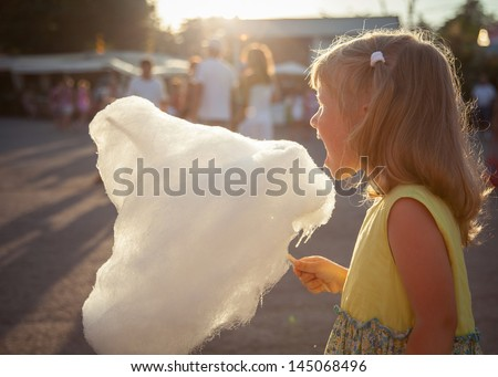 Charming little girl eating cotton candy - stock photo