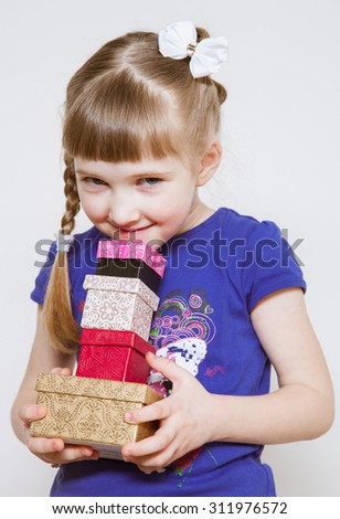 Charming little girl holding several boxes with gifts - stock photo