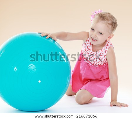 charming little girl in a pink dress rolls before a big blue ball.Concept of childhood and family values. - stock photo