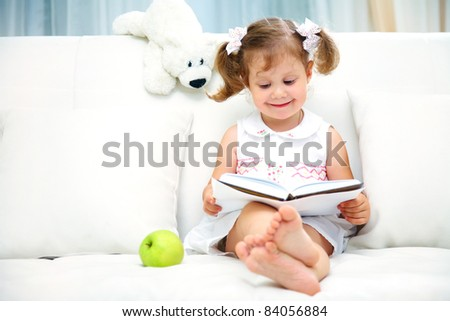 Charming little girl reading book with her toy on white sofa - stock photo