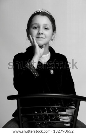 Charming little girl sitting on a chair and posing at the camera on a light background on Beauty and Fashion - stock photo