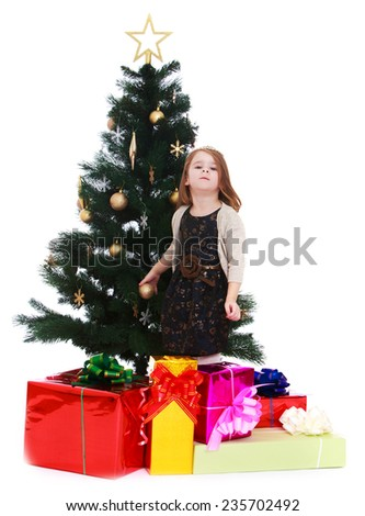 Charming little girl stands near a Christmas tree.White background, isolated photo. - stock photo
