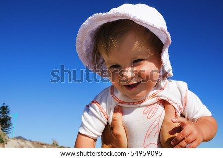 charming little happy girl laughing in the arms of his mother, against the blue sky - stock photo