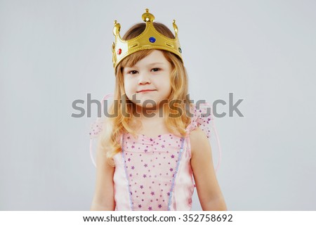 Charming little princess, with curly blond hair, wearing on pink dress, golden crown and fairy wings on her back, posing on white background, in studio, waist up - stock photo