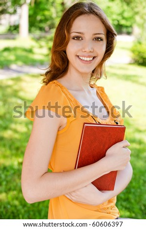 Charming long-haired girl with book. - stock photo
