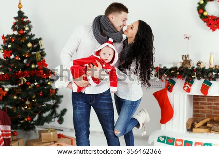 Charming man and woman, wearing in sweaters and jeans, with little baby in red costume, posing in decorated room with christmas tree on the background and have fun, waist up - stock photo