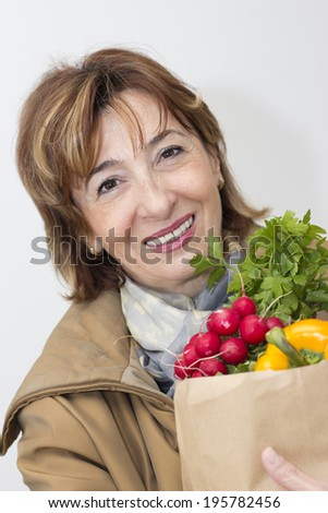 Charming mature woman holding a bag of groceries. - stock photo