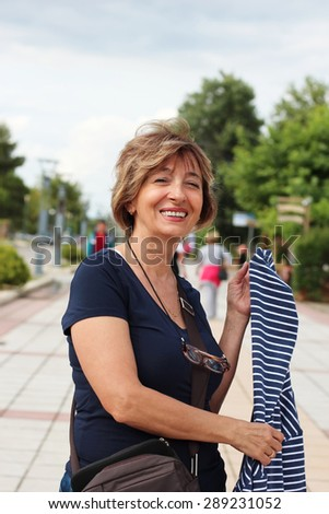 Charming mature woman posing on a sidewalk and looking at camera. People in the background.   - stock photo