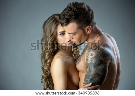 Charming model lovingly looks at tattooed man - stock photo