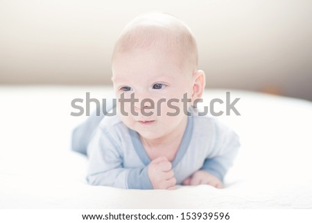 Charming newborn baby boy in blue on a bed  - stock photo